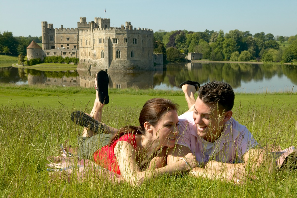 Couple enjoying a day out at Leeds Castle, relaxing in the grounds surrounding the 12th Century fortified manor house on the River Len in the heart of Kent, Leeds Castle, Maidstone, Kent, England. Additional Credit: Kent Tourism Alliance