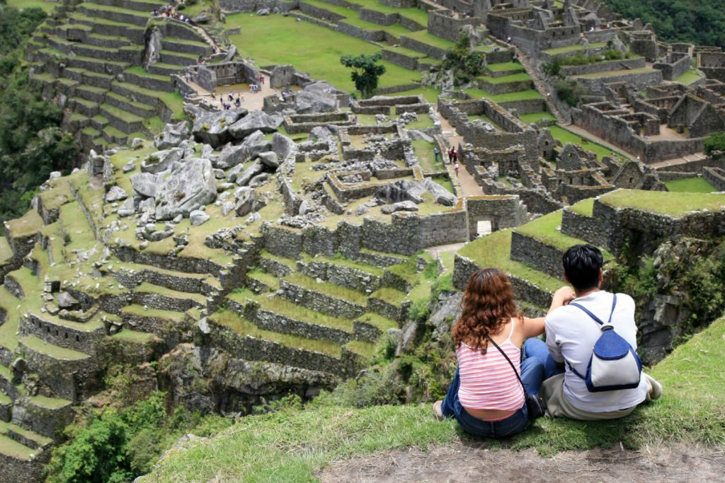 Young couple looking the famous Machu Picchu / Onfokus, Getty Images