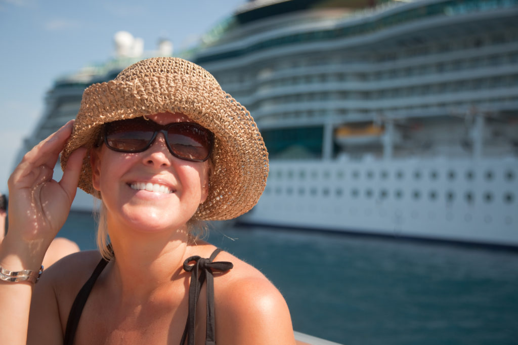 Woman on Tender Boat with Cruise Ship in the Background / By Feverpitch, Deposit Photos