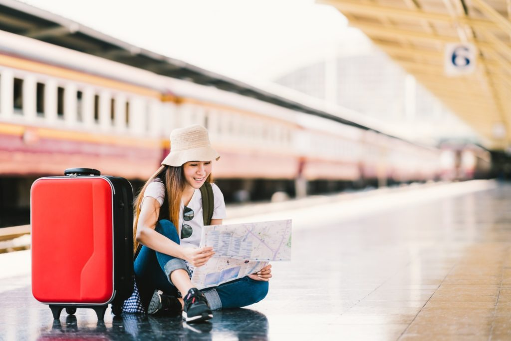 Girl with red suitcase at train station by beer5070, Deposit Photos